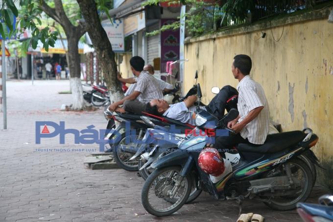 Một ông bố ung dung ngả lưng trên yên xe máy.