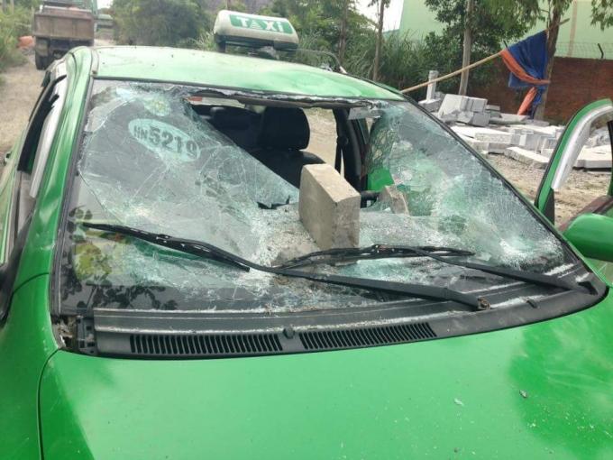 Xe taxi bị vỡ kính chắn gió phía trước và 2 kính cửa bên phải.Ảnh Facebook Tùng Lâm.