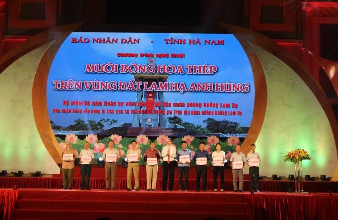 Đồng chí Đinh Thế Huynh đã trao sổ tiết kiệm cho thân nhân 10 nữ liệt sĩ dân quân phòng không xã Lam Hạ.