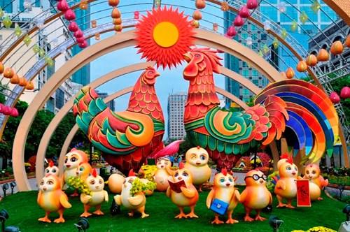 """Đường hoa Nguyễn Huệ năm nay sẽ khai mạc vào lúc 19h ngày 25/1 (tức 28 tháng Chạp). Sau đó sẽ mở cửa cho người dân vào tham quan, vui chơi kéo dài đến 22h ngày 31/1 (tức mùng 4 Tết). Trong ảnh: Đại cảnh """"Xuân sum họp"""" ở đường hoa khắc họa hình ảnh gia đình gà đầm ấm, sung túc, sum vầy, biểu tượng linh vật của năm Đinh Dậu được đặt ở vị trí trung tâm. Chú gà trống cao 3.5m, gà mái 2.8m và 15 chú gà con cao 0,6m."""