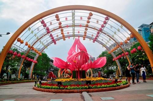 """Làm nền cho đại cảnh """"Xuân sum họp"""" là giàn đèn lồng ngày xuân cao từ 8m – 10m, rộng 10m – 11m với khoảng 108 chiếc đèn lồng được thiết kế riêng cho Đường hoa 2017 với những gam màu rực rỡ đón chào xuân Đinh Dậu đầy may mắn."""