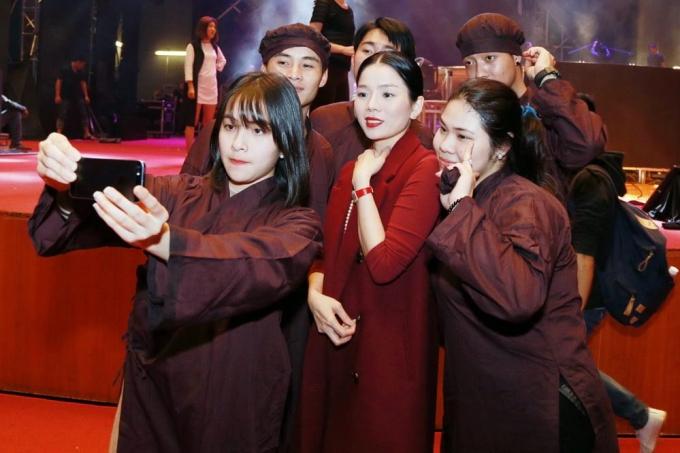 Lệ Quyên chụp hình cùng các diễn viên quần chúng trong màn tâm linh.
