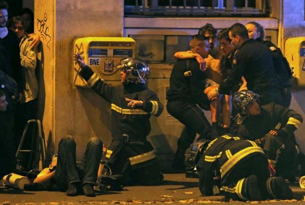 Lính cứu hỏa Pháp hỗ trợ những người bị thương sau vụ xả súng. (Ảnh: Reuters)