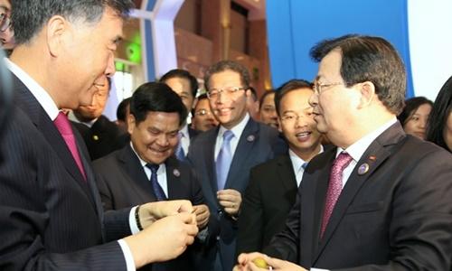 Phó thủ tướng Trịnh Đình Dũng (phải)mời Phó thủ tướng Trung Quốc Uông Dương, lãnh đạo các bộ, ngành và tỉnh Vân Nam thưởng thức vải thiều tại gian hàng nông sản Việt Nam. (Ảnh: VGP)