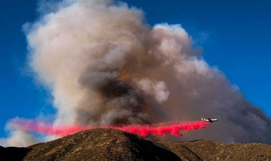 Một máy bay thả chất làm chậm cháy xuống đám cháy ở California.
