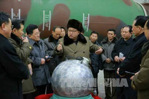 Nhà lãnh đạo Triều Tiên Kim Jong-un (giữa) trong một cuộc gặp với các nhà khoa học và kỹ thuật viên trước mô hình một phần đầu đạn hạt nhân thu nhỏ ngày 9/3. (Ảnh: Yonhap/TTXVN)