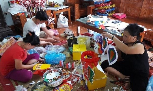 Gia đình cô Tuyến cắt dán miệt mài bên những món đồ chơi truyền thống.