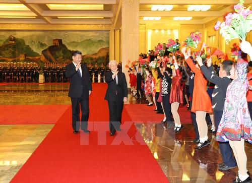 Tổng Bí thư Nguyễn Phú Trọng và Chủ tịch Trung Quốc Tập Cận Bình vẫy chào các cháu thiếu nhi tại lễ đón.Ảnh:TTXVN