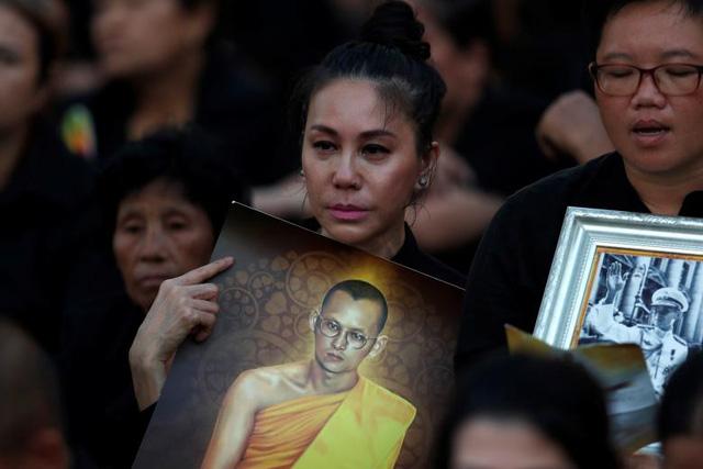Quốc vương Bhumibol Adulyadej băng hà ngày 13/10/2016 ở tuổi 88 sau một thời gian lâm bệnh nặng. Trong suốt 7 thập niên trị vì, Quốc vương được người dân yêu mến vì tài năng và đức độ, giúp Thái Lan ổn định chính trị và phát triển kinh tế mạnh mẽ như ngày nay. Trong ảnh: Người Thái mang di ảnh Quốc vương Bhumibol Adulyadej đứng chờ trước Đài hóa thân hoàng gia khi lễ hỏa táng chuẩn bị bắt đầu.