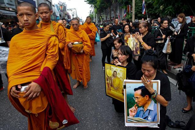 Hơn 100.000 người đã tập trung tại các tuyến đường ở thủ đô Bangkok từ ngày 25/10 để chờ đợi tang lễ của Quốc vương Bhumibol Adulyadej. Lễ rước linh cữu nhà vua từ Đại cung điện tới Đài hóa thân hoàng gia sẽ diễn ra trong sáng hôm nay. Sau đó, lễ tang cố vương sẽ tiếp tục kéo dài thêm 3 ngày. Trong ảnh: Người dân Thái quỳ gối trên đường phố Bangkok bày tỏ niềm tiếc thương với nhà vua quá cố.