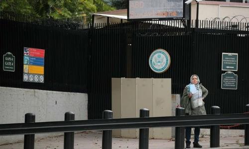 Một người phụ nữ chờ làm visa trước cổng Đại sứ quán Mỹ tại Ankara, Thổ Nhĩ Kỳ. (Ảnh: Reuters)