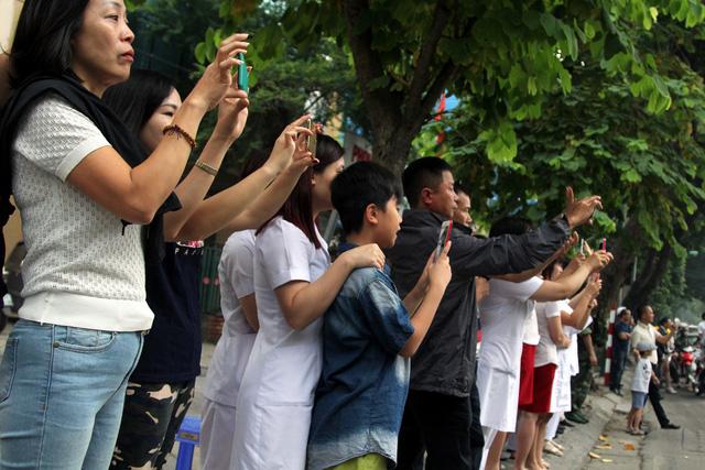 Trong lúc đoàn xe tháp tùng Tổng thống Mỹ tới Phủ chủ tịch, người dân đã tập trung dọc nhiều tuyến phố để đón và chụp ảnh đoàn.
