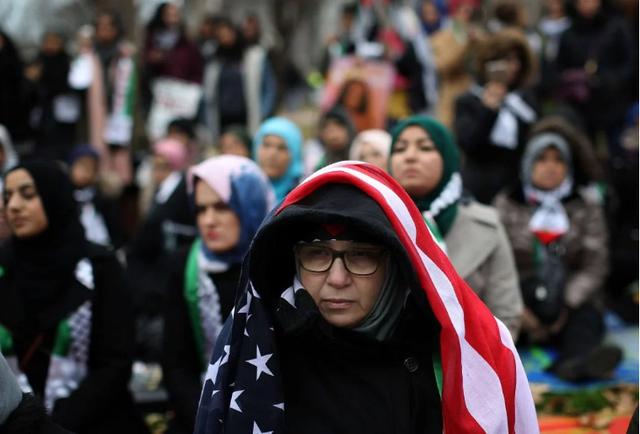 Đội khăn choàng keffiyeh truyền thống của Palestine và khăn mang màu cờ của Palestine, những người biểu tình mang theo áp phích phản đối việc Israel chiếm đóng khu vực Đông Jerusalem và Bờ Tây. (Ảnh: Getty)