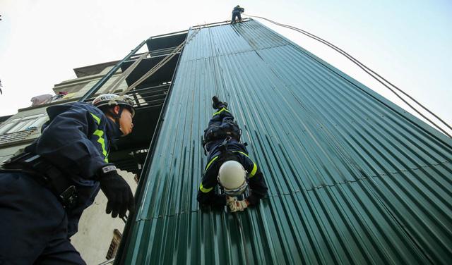 Đại uý Lan thực hiện diễn tập đu dây đầu hướng xuống đất từ độ cao tương đương toà nhà 5 tầng và tiếp đất an toàn.