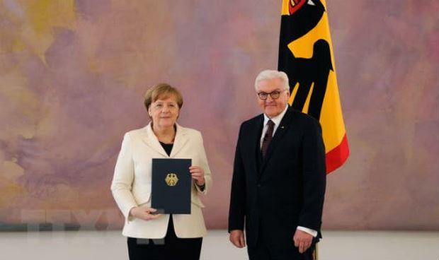 Bà Angela Merkel (trái) nhận quyết định bổ nhiệm từ Tổng thống Frank-Walter Steinmeier sau khi tái đắc cử Thủ tướng Đức