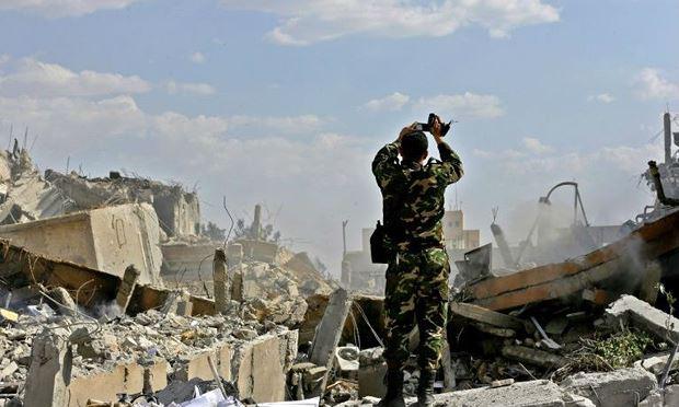 Một binh sỹ Syria kiểm tra một tòa nhà đổ nát sau cuộc không kích của Mỹ và các nước đồng minh.