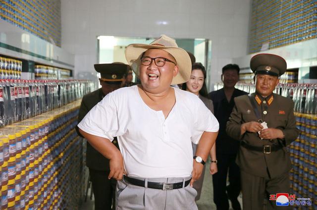 Nhà lãnh đạo Triều Tiên được nhìn thấy mặc áo thun ngắn tay cổ tròn màu trắng. Ông cũng đội một chiếc mũ rộng vành sáng màu khi tới thăm cơ sở sản xuất cá ngâm.