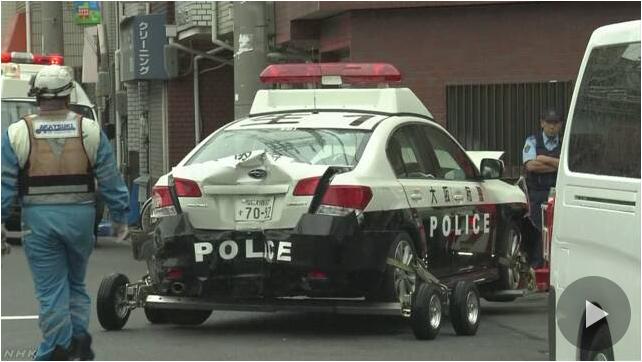 Xe của lực lượng cảnh sát Nhật Bản bị tông bẹp đuôi. (Ảnh: NHK)