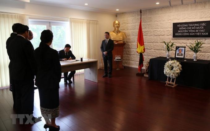 Lễ viếng và mở sổ tang nguyên Tổng Bí thư Đỗ Mười tại Australia. Đại sứ Lào tại Australia Sisavath Inphachanh đến viếng và ghi sổ tang. (Ảnh: Khánh Linh/TTXVN)