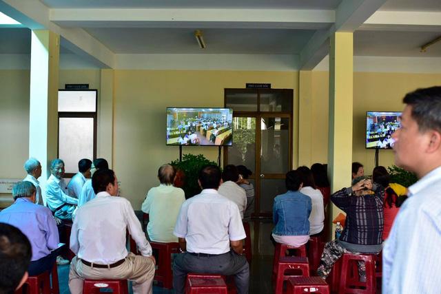 Một số người dân ngồi ngoài cửa hội trường theo dõi buổi công bố kết luận qua ti vi