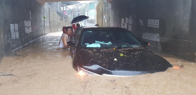 Chiếc ô tô bị mắc kẹt tại khu vực cống chui đường tàu (xóm Còi, Vĩnh Hải, Nha Trang). Ảnh: Báo Khánh Hòa