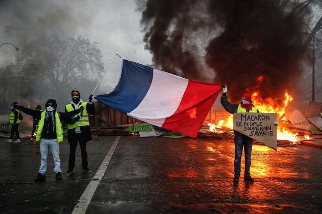 Người biểu tình Áo vàng cầm cờ Pháp phản đối chính quyền Macron tại Paris. (Ảnh: AFP)