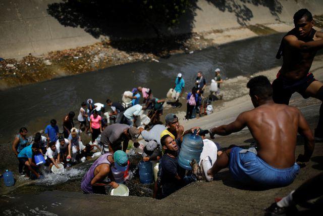 Người dân Venezuela buộc phải lấy nước từ đường ống thoát nước để đảm bảo sinh hoạt trong những ngày thiếu điện. (Ảnh: Reuters)