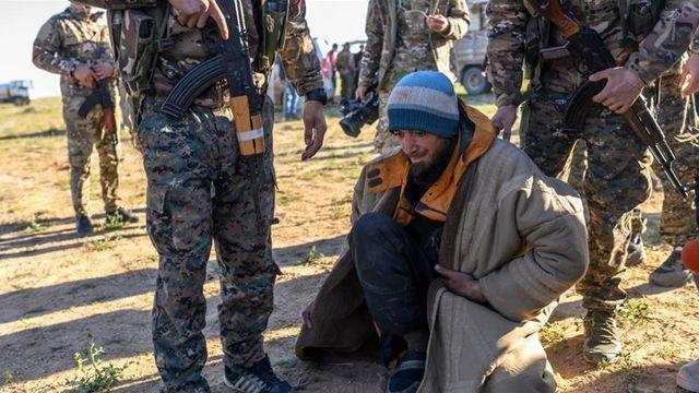 Một tay súng nghi là thành viên của IS đang bị kiểm tra tại thị trấn Baghouz, Syria (Ảnh: AFP)