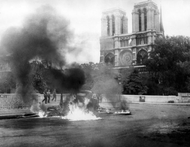 Xe bị đốt bên ngoài Nhà thờ Đức Bà Paris trong cuộc xung đột tại Pháp năm 1944. (Ảnh: AFP)