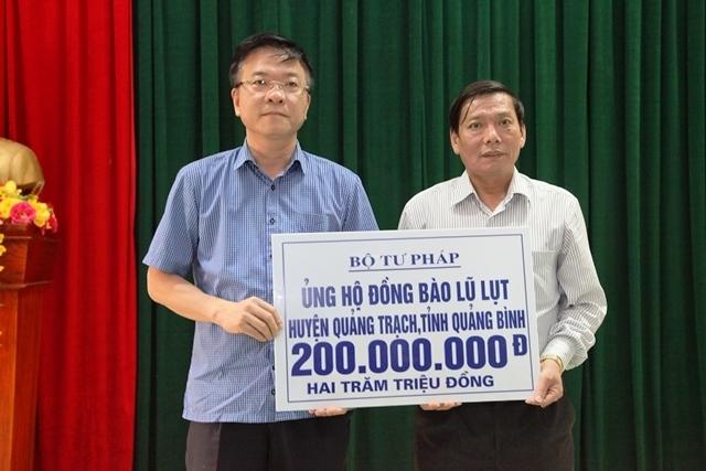 Bộ trưởng Bộ tư pháp Lê Thành Long trao quà cho đại diện nhân dân huyện Quảng Trạch, tỉnh Quảng Bình.