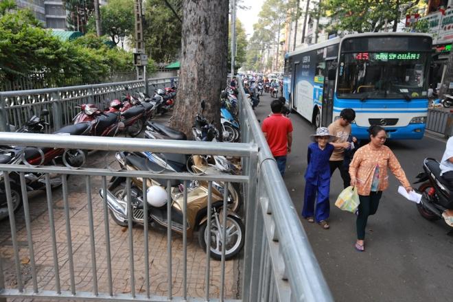 Cả đường Nguyễn Chí Thanh, Thuận Kiều sau khi rào chắn đều được tận dụng làm bãi giữ xe. Nhiều người ngại vượt qua vòng zích zắc nên đi dưới lòng đường.