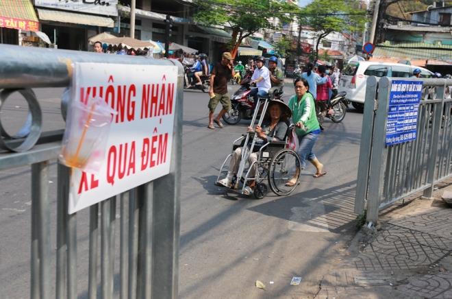 Bà Nguyễn Thị Thiện (73 tuổi) đi xe lăn bán vé số. Trước kia bà có thể lên lề đi vòng quanh vỉa hè bán. Nhưng từ ngày lắp rào chắn, bà buộc phải bán hàng dưới lòng đường.