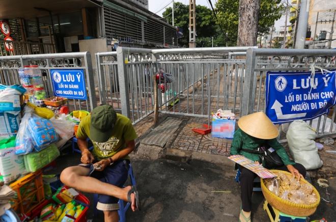 Ở cổng chính bệnh viện, tình trạng hàng rong còn bát nháo hơn. Những người bán hàng bày biện đủ hàng hóa, bàn ghế và ngồi chắn ngay cả lối vào vỉa hè.
