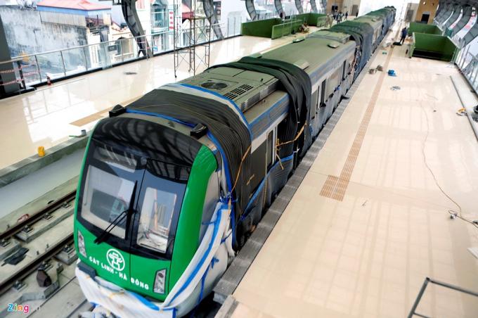 Đoàn tàu tuyến Cát Linh-Hà Đông được lắp đặt lên hệ thống ray đã 2 tháng nhưng đến nay mới lộ diện sau khi công nhân mở các tấm vải xốp phủ xung quanh.