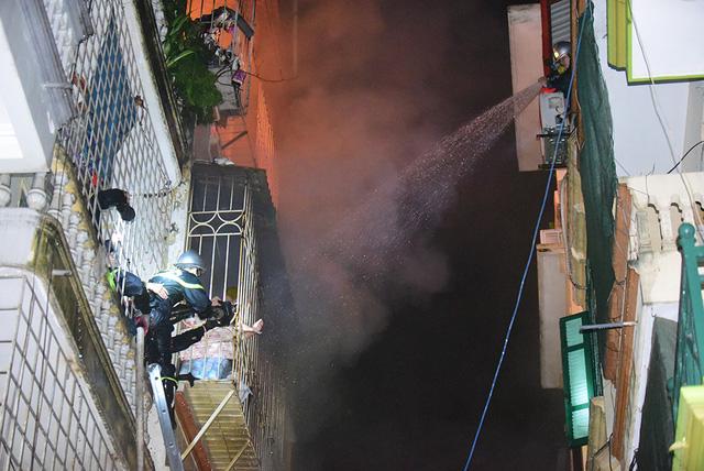 5 xe cứu hoả được điều đến hiện trường. Ngõ hẹp, cảnh sát PCCC phải tận dụng cả tầng cao nhà đối diện để phun nước dập lửa.