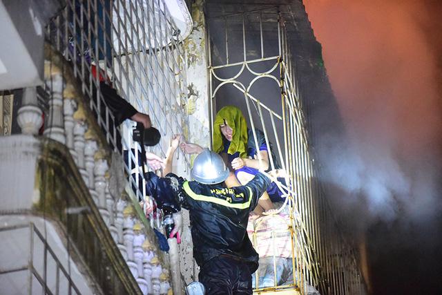 Từ nhà bên cạnh, cảnh sát PCCC cắt sắt để tiếp cận sang tầng trên cùng của ngôi nhà cháy. Tới 4h sáng, nạn nhân đầu tiên được đưa ra khỏi đám cháy.