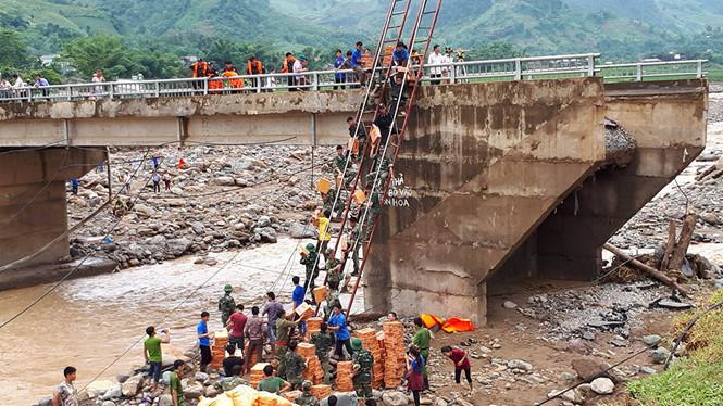 Cầu bị lũ chặt đứt, thanh niên bắc thang vận chuyển gạo nước vào vùng bị cô lập.