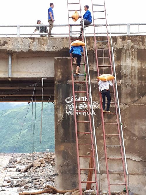 Từ lòng suối lên mặt cầu cao hàng chục mét, thanh niên vừa cõng gạo, vừa phải leo thang.