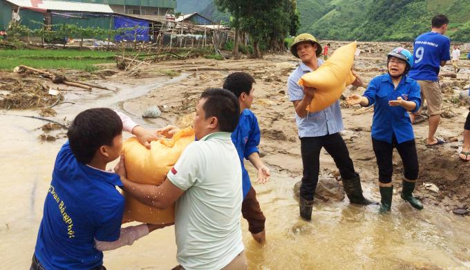 Đường đi gặp nhiều con suối, thanh niên tình nguyện đứng làm cầu vận chuyển lương thực, đẩy nhanh tiến độ tiếp tế.