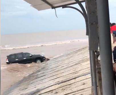 Chiếc xe đã có lúc gần như bị trôi xuống biển khiến du khách thót tim.