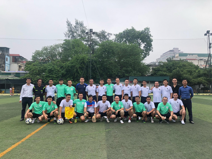 Đội bóng Liên quân các nhà báo tại Hà Nội (áo xanh) chụp ảnh lưu niệm cùng đội chủ nhà Công an phường Láng Thượng.