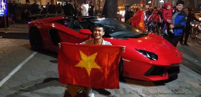 Một chiếc siêu xe màu đỏ trên phố Hai Bà Trưng, Hà Nội được người hâm mộ vây quanh chụp ảnh lưu niệm.