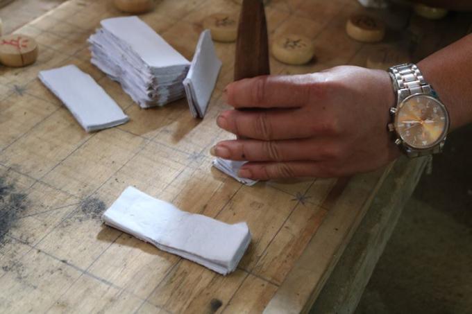 Thầy cúng đóng dấu vào những tờ giấy được cho là tiền âm phủ.