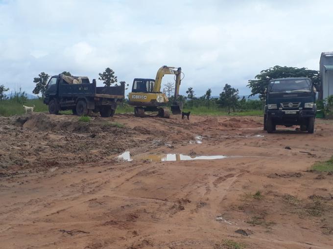 Máy múc và xe tải chở cát đang đậu sát điểm hút cát trái phép.