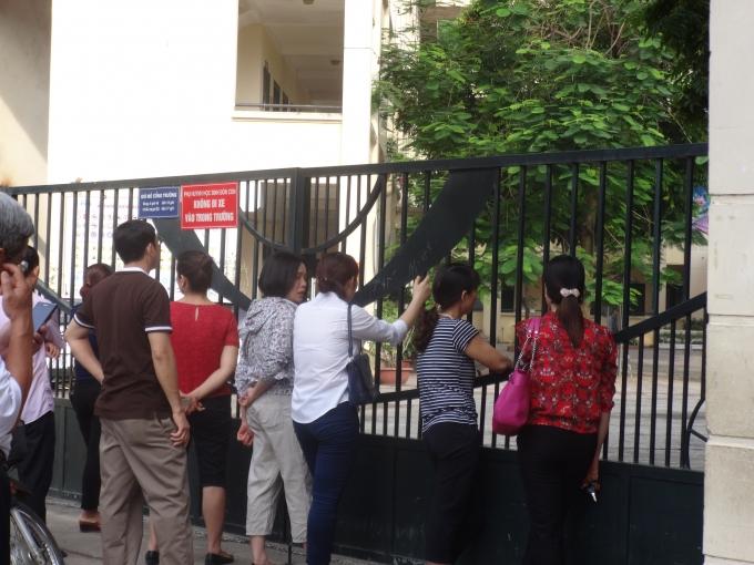 Dù con đã vào phòng thi, nhưng nhiều phụ huynh vẫn đứng chờ, cố gắng nhìn qua cánh cửa đế tìm đến phòng thi của con.