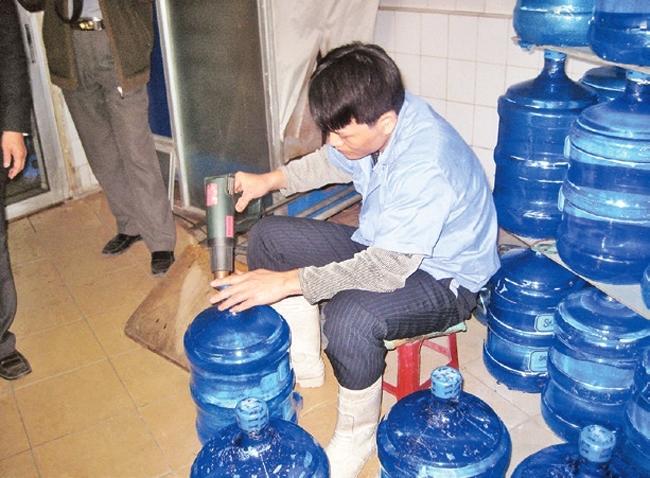 Đóng bình nước một cách thủ công, không tuân thủ quy định vệ sinh tại một cơ sở cung cấp nước