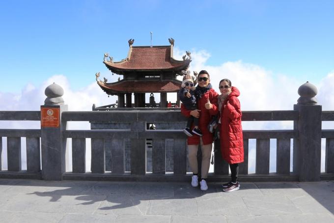 Còn gia đình nhỏ của Quốc Cơ thì không thể bỏ lỡ cơ hội cùng nhau chụp ảnh kỉ niệm bên bầu trời xanh ngắt, mây trắng vây quanh trong khung cảnh cổ kính, phía xa là Đài Gác Đại Hồng Chung với lầu chuông tám mái nổi tiếng.