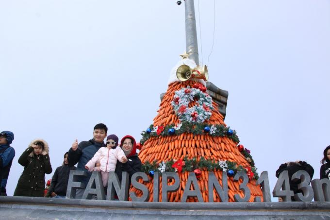 Và trên đỉnh Fansipan, dưới chân cột cờ là một cây thông khác được kỳ công kết từ 1,2 tấn cà rốt đỏ tươi, rực sáng như đốm lửa ấm áp trên Nóc nhà Đông Dương.