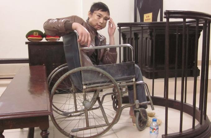 Bị cáo Tân trên chiếc xe lăn ngồi co rúm trước vành móng ngựa.