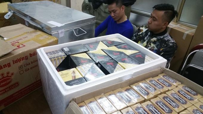 Hai đối tượng bị bắt giữ cùng với số lượng khủng thuốc lá, xì gà lậu